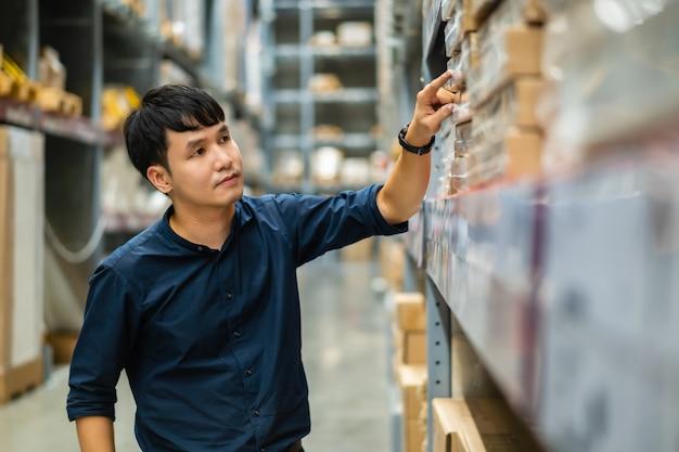 Operaio del giovane che controlla l'inventario nel deposito del magazzino