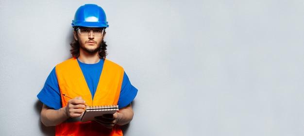 Giovane, ingegnere lavoratore che indossa attrezzature per l'edilizia di sicurezza, scritto in taccuino su sfondo di parete grigia strutturata con spazio di copia. vista panoramica del banner.