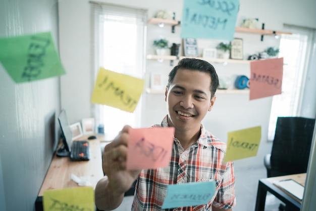 Il lavoratore del giovane scrive le note di carta sulla parete di vetro