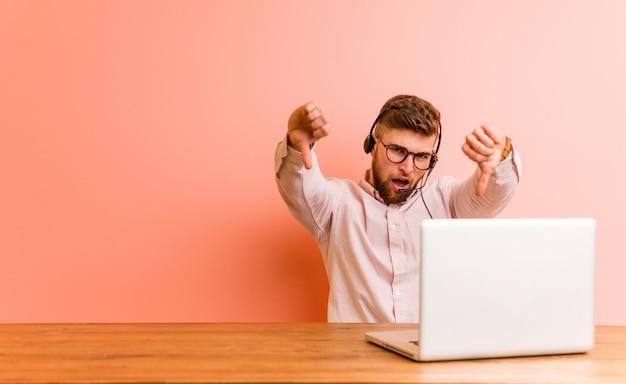 Giovane che lavora in un call center che mostra il pollice verso il basso e che esprime antipatia.