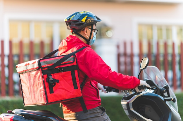 Giovane che lavora per un servizio di consegna di cibo che controlla con la moto da strada in città