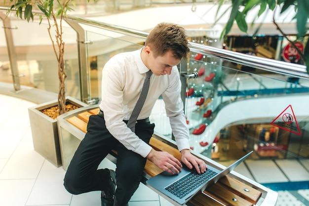 Giovane che lavora al taccuino, in camicia bianca, seduto su una sedia, studente serio, imparando al computer