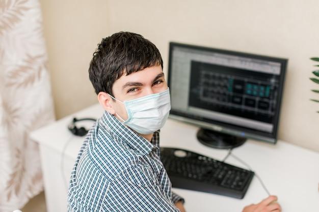 Giovane che lavora a un tavolo con un computer sul suo posto di lavoro. lavorare da casa durante la quarantena. indossa una maschera