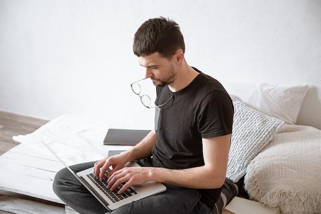 Un giovane uomo lavora a distanza dietro un laptop a casa. freelance e concetto di internet.