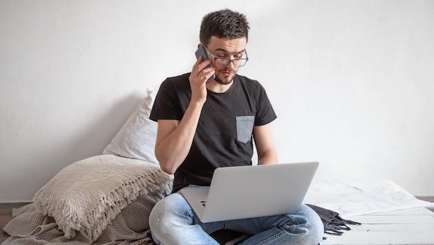 Un giovane uomo lavora in remoto dietro un computer portatile a casa sulla parete interna della stanza leggera. freelance e concetto di internet.