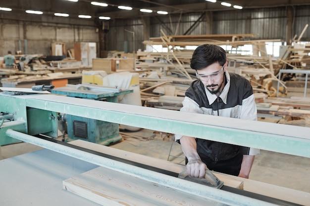 Giovane uomo in abiti da lavoro chinarsi sul banco di lavoro e levigare la superficie del pezzo in lavorazione con utensile manuale in legno mentre si lavora in fabbrica