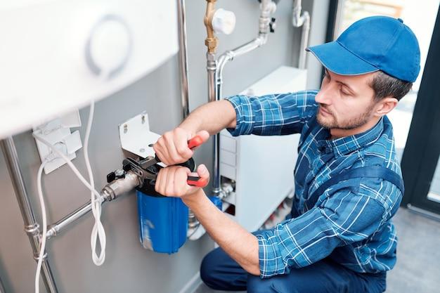 Giovane uomo in abiti da lavoro utilizzando una pinza durante l'installazione del sistema di filtraggio dell'acqua nella cucina del cliente