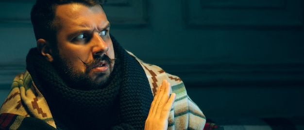 Il giovane avvolto in un plaid sembra malato starnutisce e tossisce seduto sul divano di casa al chiuso