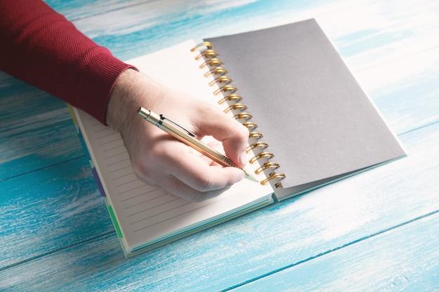 Un giovane scrive su un taccuino
