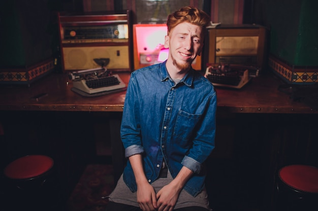 Scrittura del giovane sulla vecchia macchina da scrivere. con illuminazione scura, ristorante, abiti moderni, vecchie abitudini di scrittore