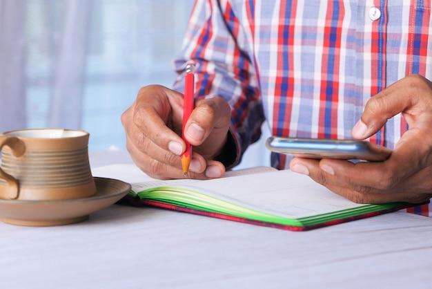 Giovane che scrive e utilizza smart phone sulla scrivania in ufficio