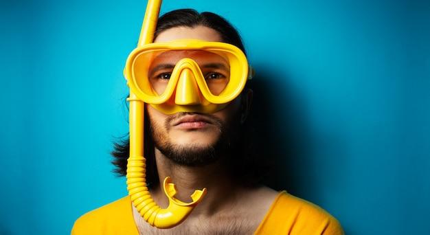 Giovane in giallo, indossando maschera subacquea e boccaglio su sfondo blu.