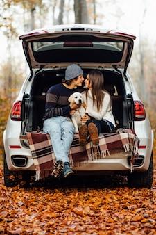 La giovane coppia sposata fa un picnic con il loro piccolo labrador in automobile nella foresta autunnale.