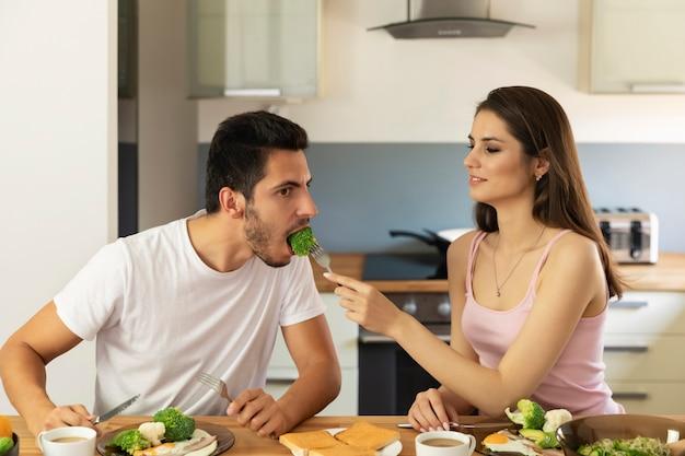Una giovane coppia sposata che fa colazione a casa