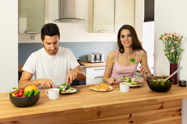 Giovane coppia di sposi facendo colazione a casa