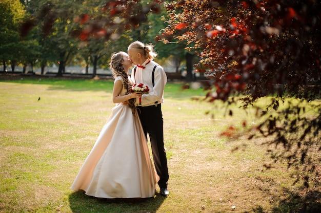Giovani coppie sposate che baciano su un campo di erba verde con un albero in una priorità alta
