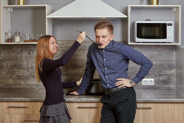 Giovane coppia di sposi in cucina nel loro appartamento.