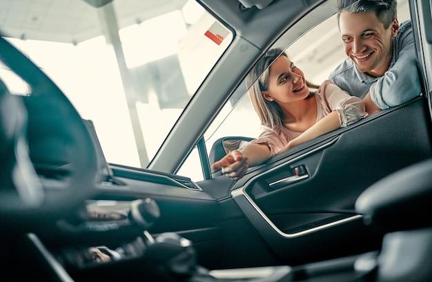 La giovane coppia sposata esamina un'auto in una concessionaria di automobili. acquisto e noleggio auto.