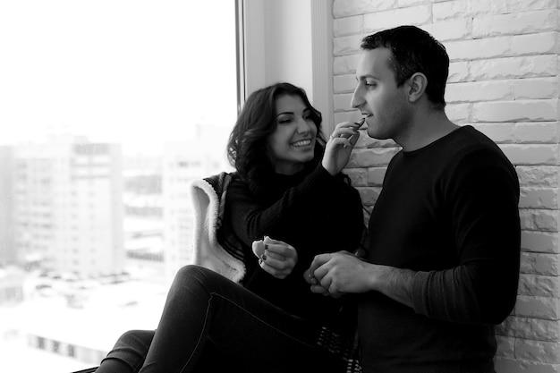 Una giovane coppia di sposi guarda fuori dalla finestra di un nuovo appartamento