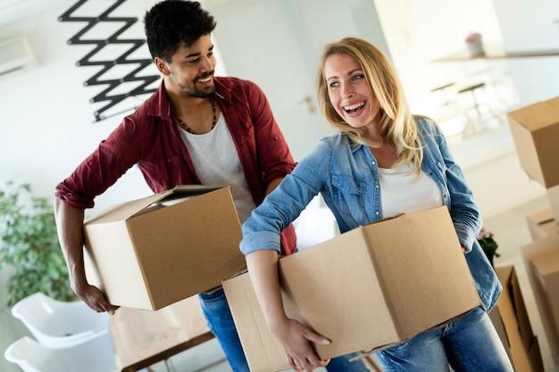 Giovane coppia sposata che si trasferisce in una nuova casa e disimballa scatole di cartone