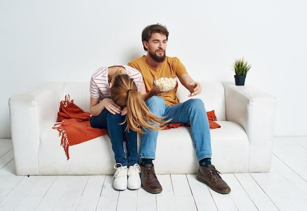Giovane coppia sposata che si rilassa a casa sul divano intrattenimento popcorn