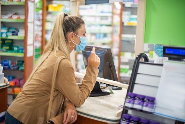 Giovane donna mascherata che controlla in una farmacia, concetto di coronavirus
