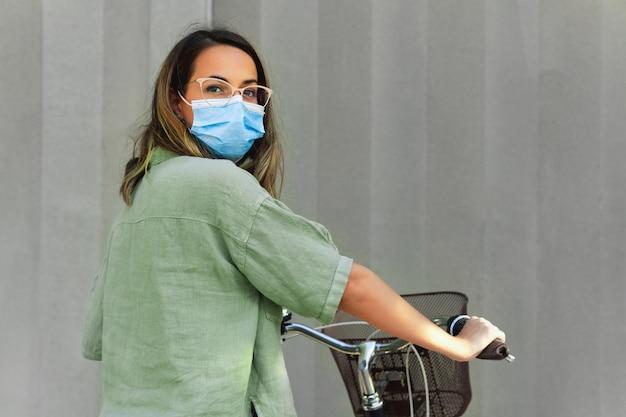Giovane donna mascherata che tiene una bicicletta in uno sfondo grigio