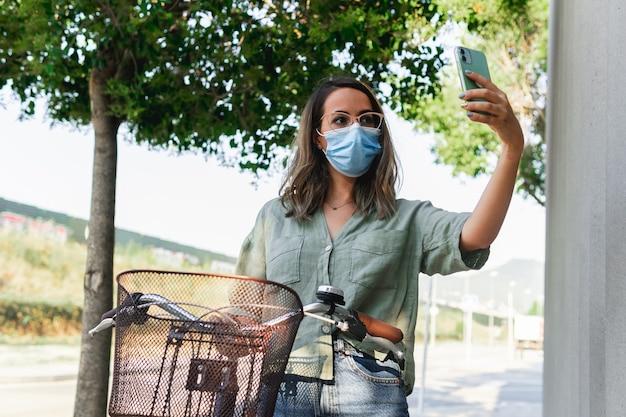 Giovane donna mascherata che fa un selfie mentre si tiene una bicicletta