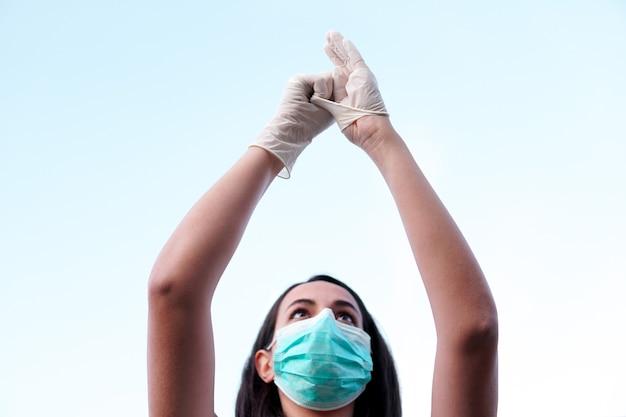 Una giovane donna mascherata che indossa guanti protettivi con il cielo sullo sfondo