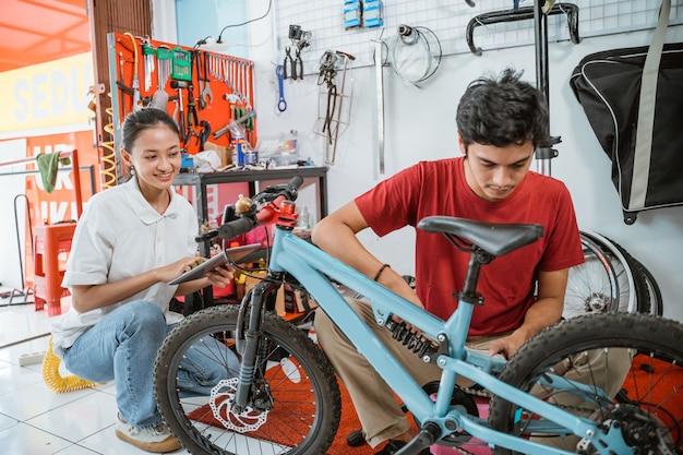 Giovane meccanico che monta una nuova bicicletta usando una chiave inglese nel negozio