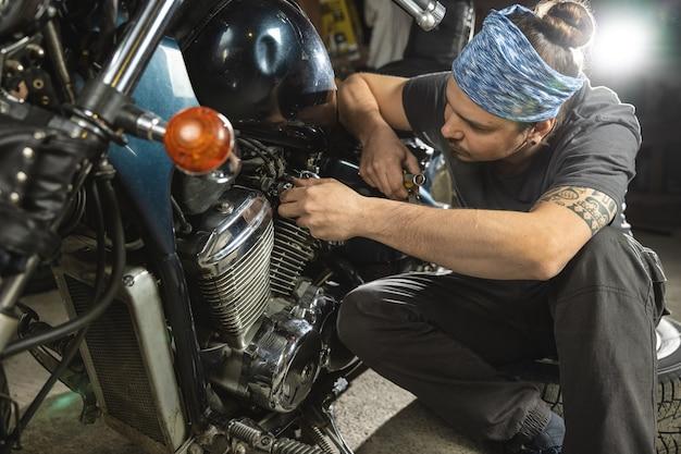 Un giovane meccanico in una bandana ripara una moto d'epoca ritratto in primo piano