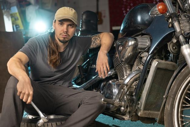 Un giovane meccanico ripara una moto d'epoca ritratto in primo piano