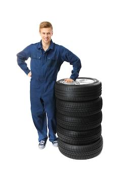 Giovane meccanico in uniforme con ruote isolate