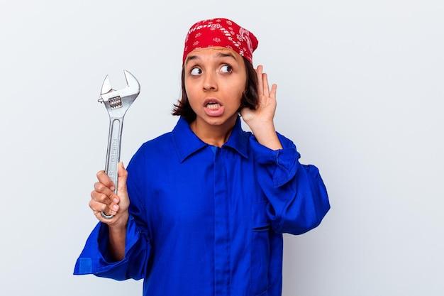 Giovane donna meccanica che tiene una chiave isolata che prova ad ascoltare un pettegolezzo.