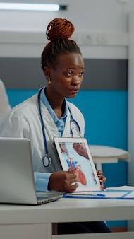 Giovane medico che tiene compressa con cardiogramma medico
