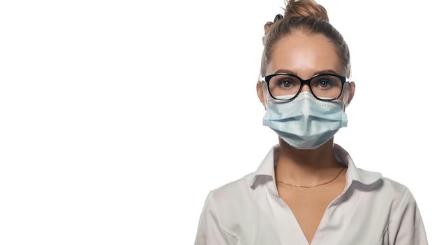 Giovane medico in maschera guardando dritto.