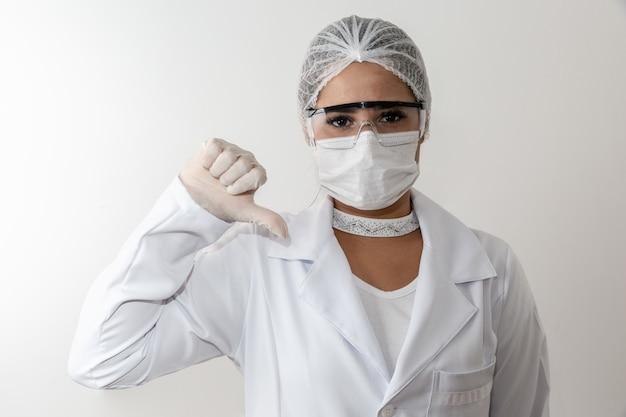 La giovane donna medica che compone i pollici giù firma