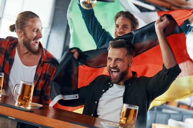 Giovani uomini coperti di bandiere internazionali che si godono la birra mentre guardano una partita sportiva al pub