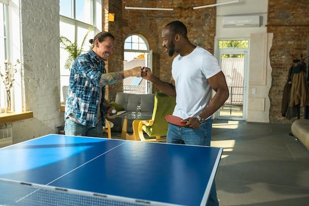 Giovani uomini che giocano a ping pong sul posto di lavoro, divertendosi
