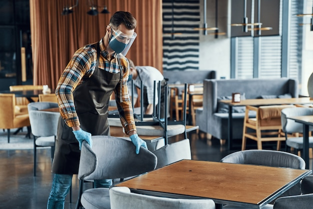 Giovani uomini in visiere protettive e grembiuli che sistemano i mobili nel ristorante
