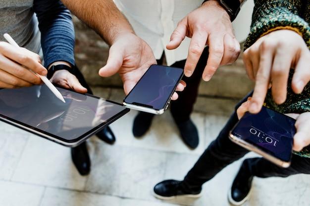 Giovani uomini che usano dispositivi digitali