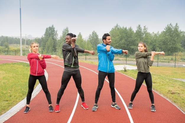 Giovani uomini e donne in abbigliamento sportivo in piedi sulle piste di uno stadio all'aperto e si allenano insieme