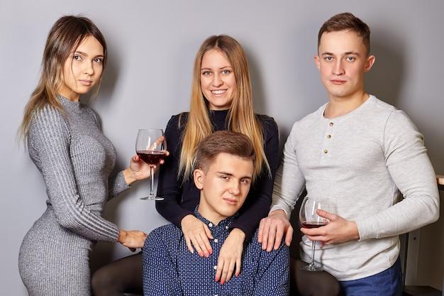 Giovani uomini e donne, con bicchieri di vino in mano, fanno ritratti di gruppo dopo la festa.