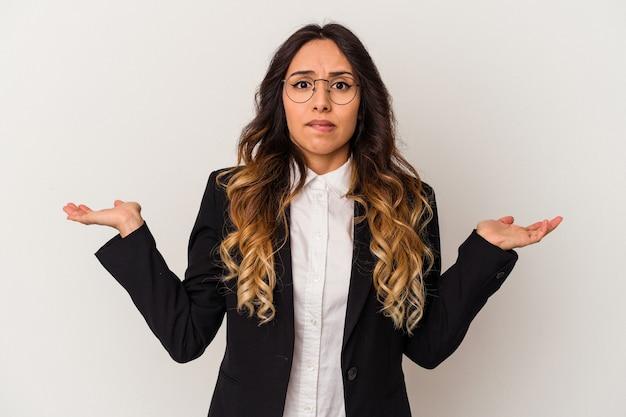 Giovane donna messicana di affari isolata su fondo bianco confuso e dubbioso che scrolla le spalle per tenere uno spazio della copia.