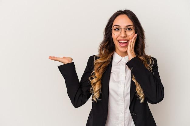 La giovane donna messicana di affari isolata su fondo bianco tiene lo spazio della copia su una palma, tiene la mano sulla guancia. stupito e deliziato.
