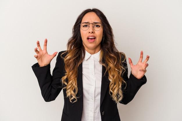 Giovane donna messicana di affari isolata su fondo bianco che grida con rabbia.