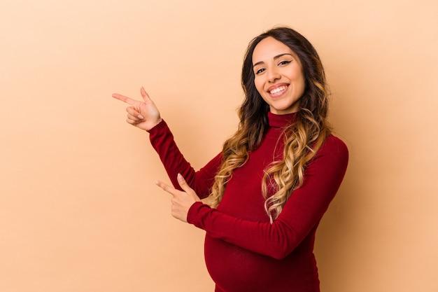 La giovane donna incinta messicana isolata su fondo beige eccita il puntamento con gli indici di distanza.