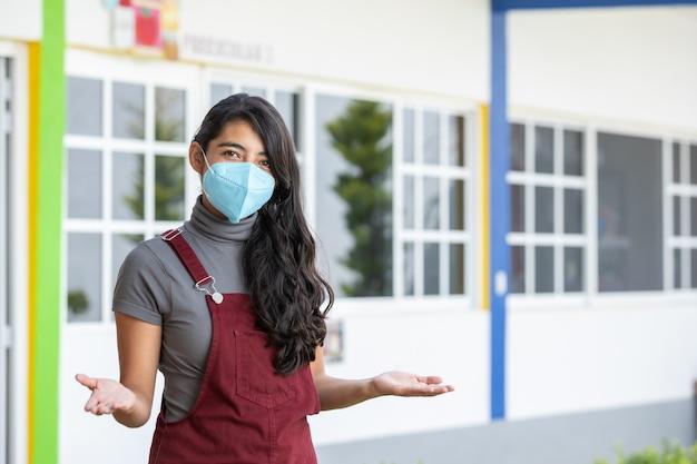 Giovane insegnante messicana che indossa la maschera bentornata a scuola, nuova normalità