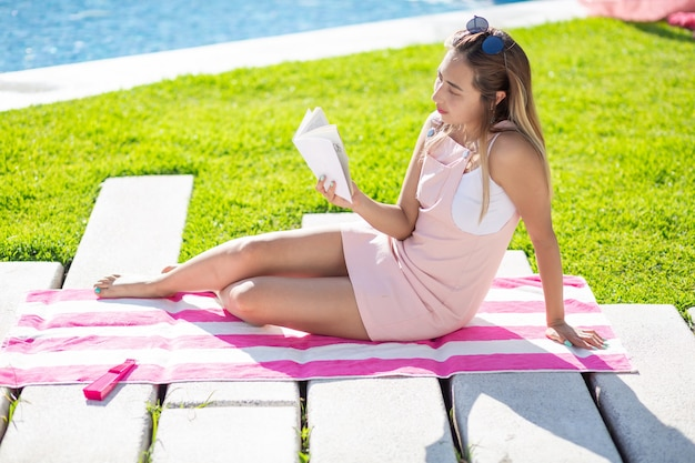 Giovane donna messicana in abito che legge sul bordo della piscina in una giornata di sole