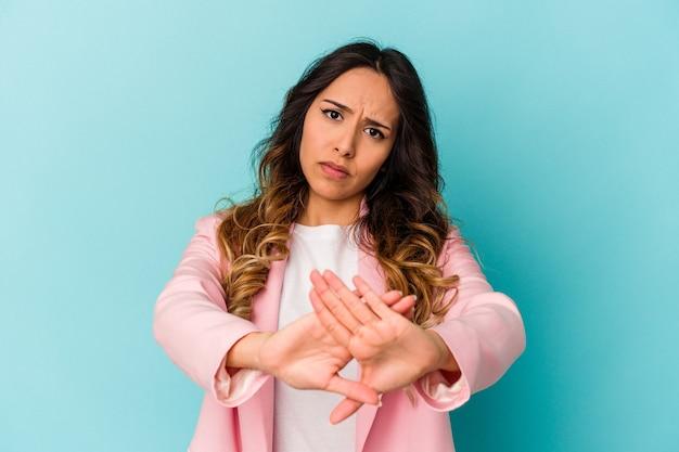 Giovane donna messicana isolata su sfondo blu facendo un gesto di rifiuto
